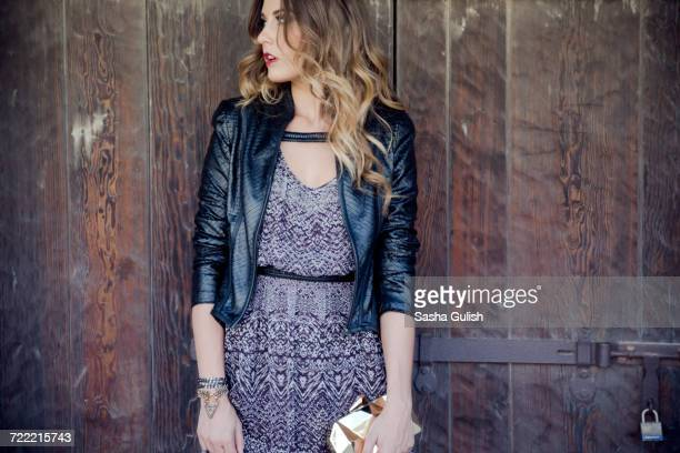 stylish young woman looking over her shoulder from wooden door - leather dress stock pictures, royalty-free photos & images