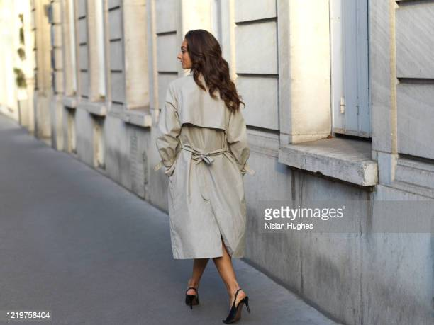 stylish young woman on sidewalk daytime, paris france - trench coat stock pictures, royalty-free photos & images
