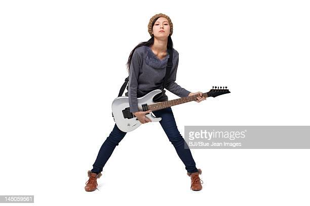 Stylish young woman playing guitar