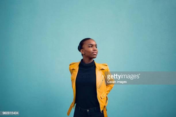 stylish young woman posing against blue wall - veste et blouson photos et images de collection