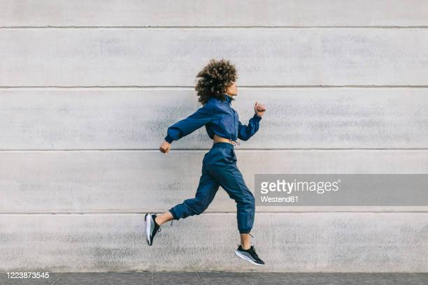 stylish young woman running along concrete wall - sportswear stock pictures, royalty-free photos & images