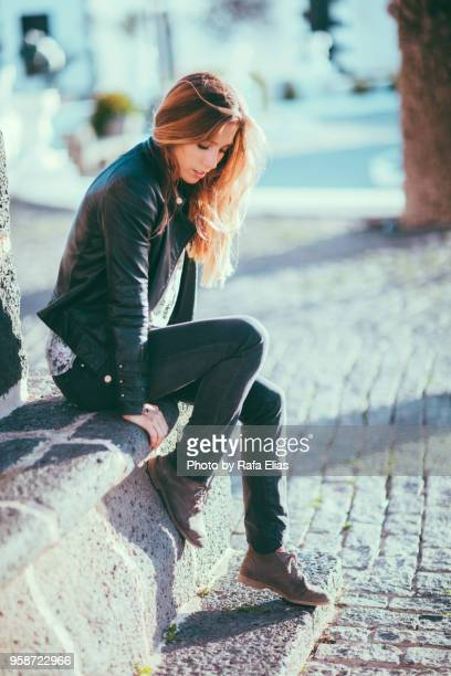 Stylish young woman sitting on cement bench