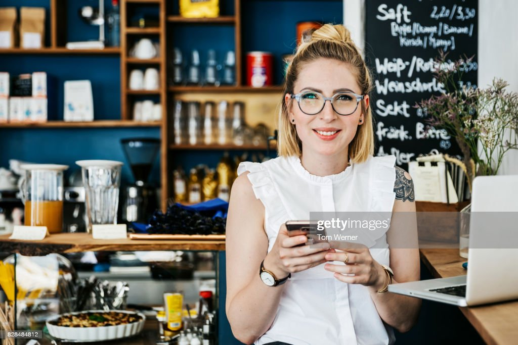 "Stylish Young Woman Smiling Using Smartphone In Cafe""n : Stock Photo"