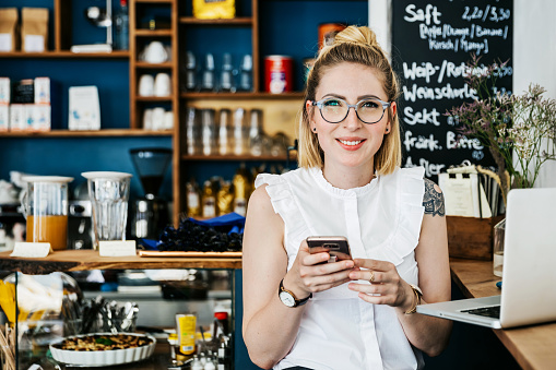 Stylish Young Woman Smiling Using Smartphone In Cafe'n - gettyimageskorea