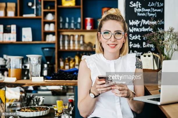 "stylish young woman smiling using smartphone in cafe""n - jeune femme blonde photos et images de collection"