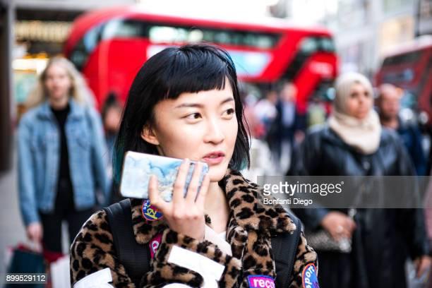 Stylish young woman strolling on street making smartphone call, London, UK