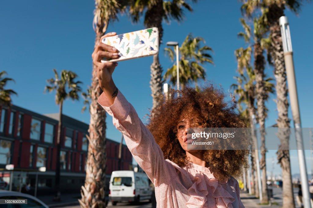 Stylish young woman taking a selfie at seaside promenade : Stock Photo