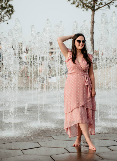 Stylish Young Woman Trying To Stay Cool In Summer In Front Of Streams Of Water From A Flat Fountain.