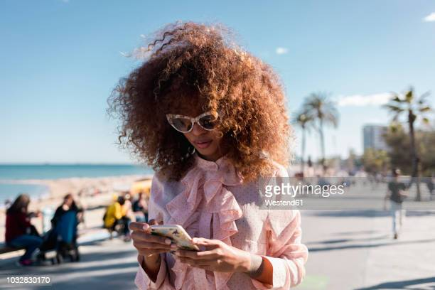 stylish young woman using cell phone at seaside promenade - blouse stockfoto's en -beelden