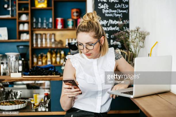 stylish young woman using smartphone while working at cafe - blonde glasses stock-fotos und bilder