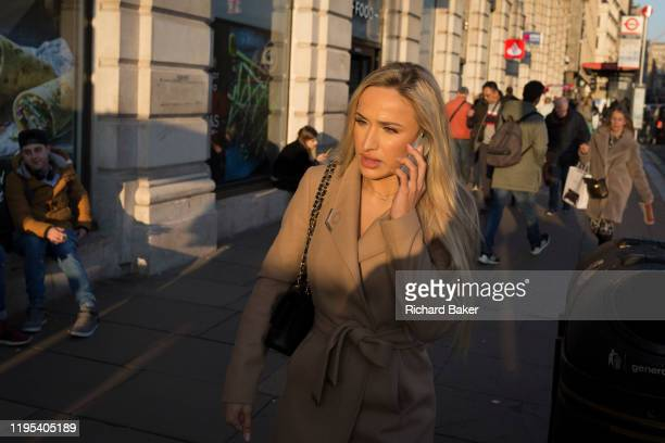 Stylish young woman walks and talks into her phone on Piccadilly, on 21st January 2020, in London, England.