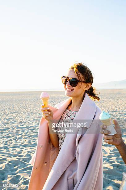 Stylish young woman with boyfriend eating ice cream cone strolling on beach, Venice Beach, California, USA