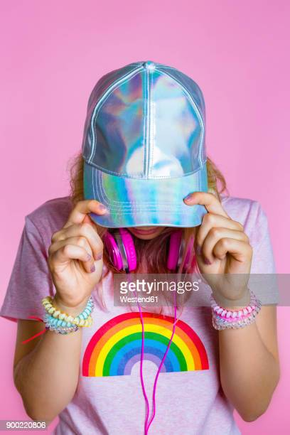 Stylish young woman with headphones hiding her face behind basecap in front of pink background
