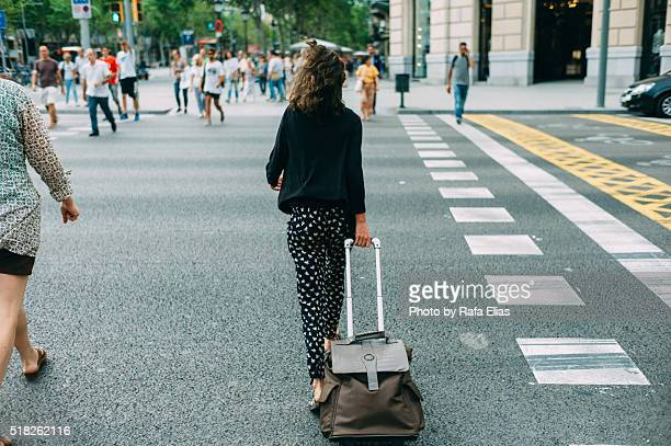 stylish young woman with suitcase with wheels walking on zebra crossing - paso de cebra fotografías e imágenes de stock