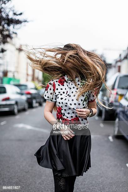 stylished young woman shaking her hair - windswept stock pictures, royalty-free photos & images