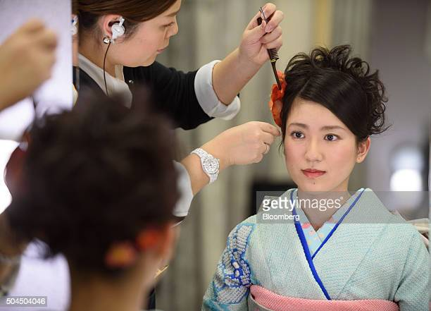A stylist affixes a floral ornament into the hair of a young woman dressed in a furisodestyle kimono for her Coming of Age Day ceremony at a photo...