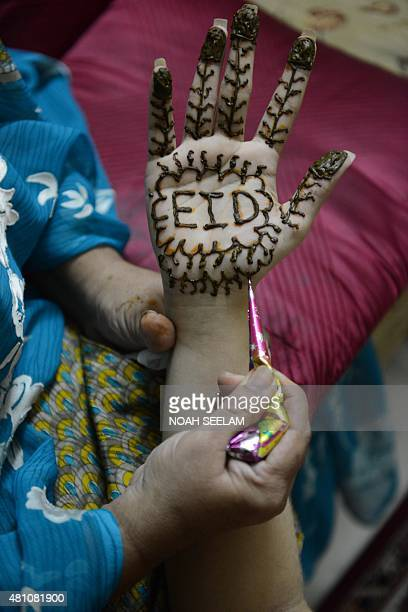 A stylist applies mehendi on the hand of Muslim woman Feroze Jahan Begum designed with Eid Mubarak wishes during 'Chand Raat' or 'Night of the Moon'...