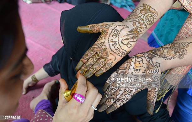 A stylist applies mehendi on the hands of a customer during 'Chand Raat' or 'Night of the Moon' in Hyderabad on August 8 traditionally held on the...