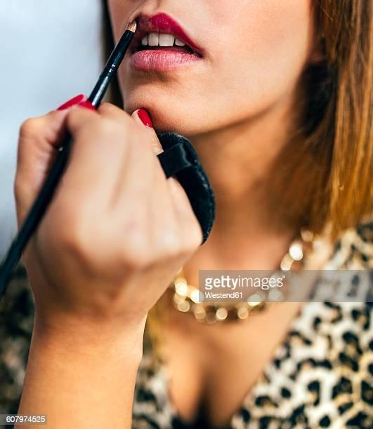 Stylist applying lipstick in beauty salon
