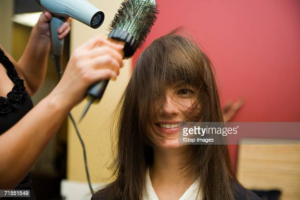 A stylist blow drying a young woman?s hair