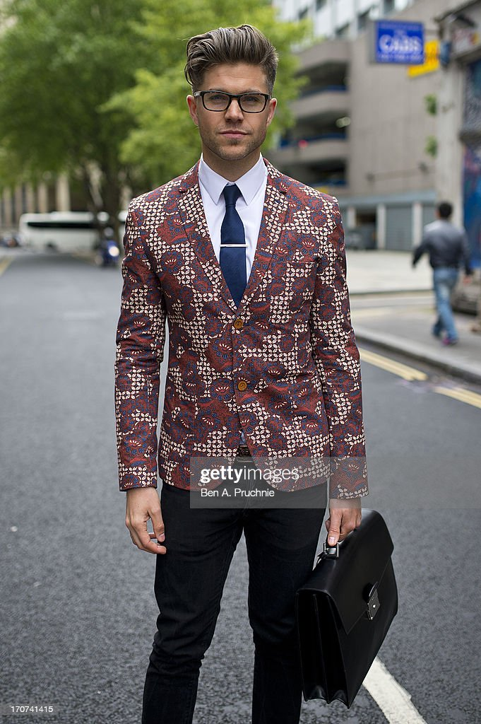 Stylist Darren Kennedy (32) poses wearing a Topman Blazer, Reiss shirt, Ted Baker tie, H+M jeans with Shore Leave shoes a swatch watch and a Prada satchel at the YMC Caltwalk presentation held during London Collections:MEN SS14 at The Old Sorting Office on June 17, 2013 in London, England.