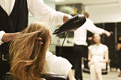 Stylist Drying Girl's Hair With Hair Dryer In Beauty Salon