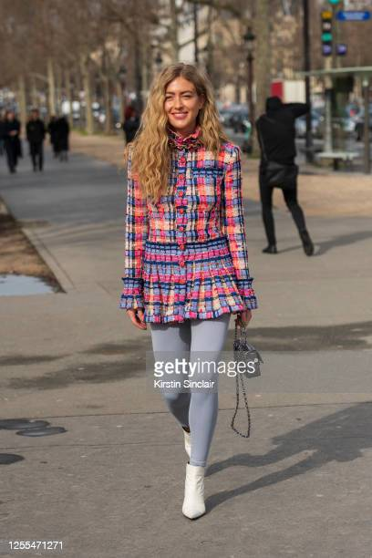 Stylist Emilie Sindlev wears a Chanel top and bag, H20 Fagerholt leggings and white boots on March 03, 2020 in Paris, France.
