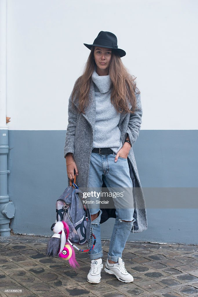 Stylist Estelle Pigault wears a River Island coat, Chanel trainers, ACNE jeans, Primark sweater, vintage hat, and Chanel backpack on day 2 of Paris Haute Couture Fashion Week Spring/Summer 2015, on January 26, 2015 in Paris, France.