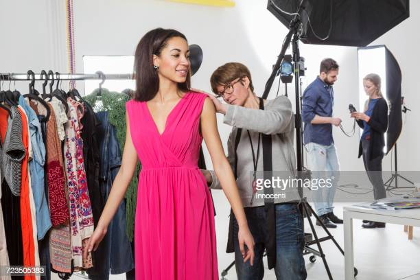 Stylist fastening fashion models dress in photography studio