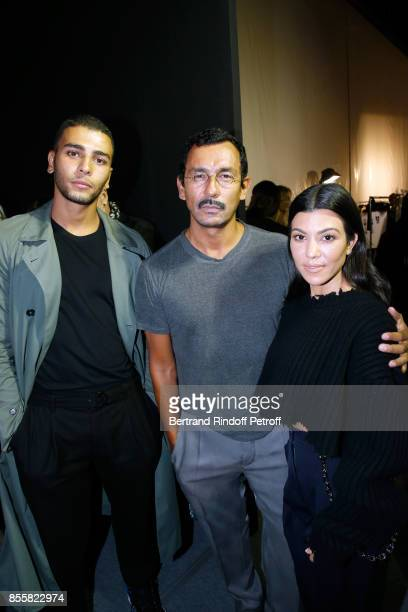 Stylist Haider Ackermann standing between Kourtney Kardashian and her companion Younes Bendjima pose Backstage after the Haider Ackermann show as...