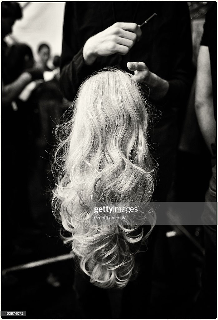 A stylist holds a wig backstage at the Art Hearts Fashion Presented By AIDS Healthcare Foundation fashion show during Mercedes-Benz Fashion Week Fall 2015 at The Theatre at Lincoln Center on February 19, 2015 in New York City.