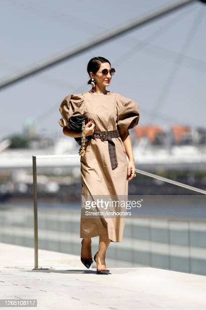Stylist Laila Hamidi wearing a long brown dress with puffy sleeves by H&M, a black chain pouch bag by Bottega Veneta, black and brown pumps by...