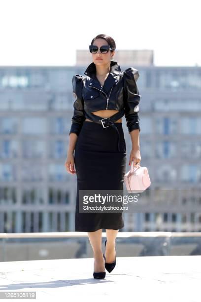 Stylist Laila Hamidi wearing black sunglasses, a short black leather jacket by Asos, a black midi length pencil skirt, black pumps and a pink bag...