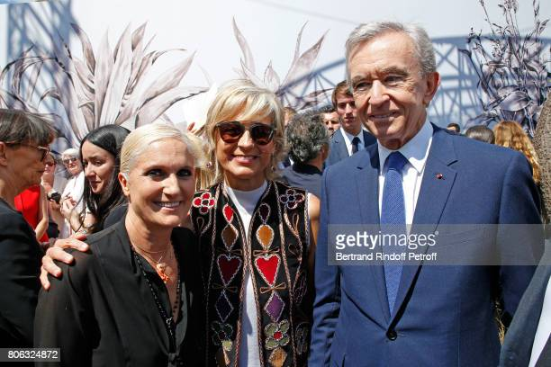 Stylist Maria Grazia Chiuri, Owner of LVMH Luxury Group Bernard Arnault and his wife Helene Arnault pose backstage after the Christian Dior Haute...