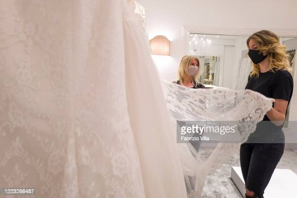 Stylist Mariella Gennarino assists a client who is soon to get married while she chooses a wedding dress in the atelier in Catania open to the public...