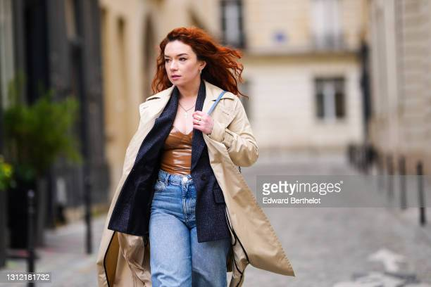 Stylist Nastasia Iavorscaia @a.la.rousse , wears a beige trench long coat from Sportmax, a navy blue wool blazer jacket from Maje, a brown shiny...