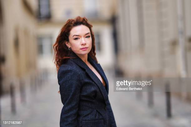 Stylist Nastasia Iavorscaia @a.la.rousse , wears a navy blue wool blazer jacket from Maje, earrings, on April 11, 2021 in Paris, France.