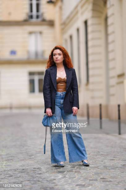 Stylist Nastasia Iavorscaia @a.la.rousse , wears a navy blue wool blazer jacket from Maje, a brown shiny low-neck body suit made of polyurethane /...