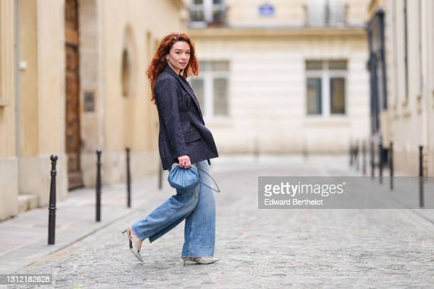 Stylist Nastasia Iavorscaia @a.la.rousse , wears a navy blue wool blazer jacket from Maje, blue denim jeans flared pants from Sandro, a blue...