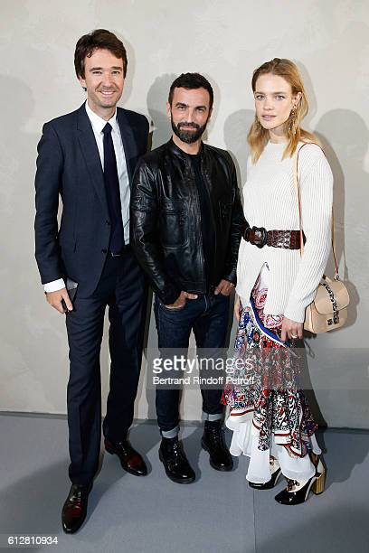 Stylist Nicolas Ghesquiere standing between General manager of Berluti Antoine Arnault and Natalia Vodianova pose after the Louis Vuitton show as...