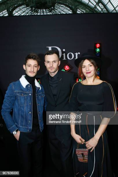 Stylist of Dior Men Kris Van Assche standing between Pierre Niney and Natasha Andrews pose after the Dior Homme Menswear Fall/Winter 20182019 show as...