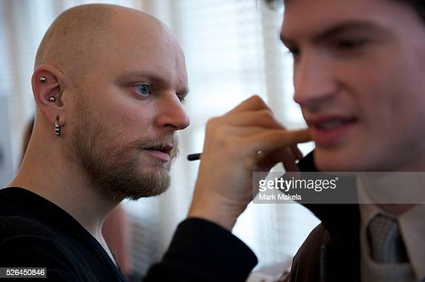 A stylist prepares a model with neck makeup before the E Tautz autumn 2011 collection at the Royal Opera House in London on 23 February 2011