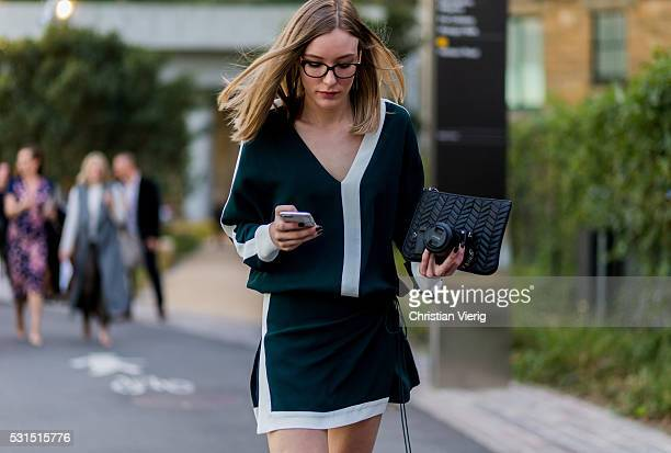 Stylist Rachele Edson wearing Josh Goot and glasses and a black clutch while writing a text message on her phone outside Toni Maticevski at...