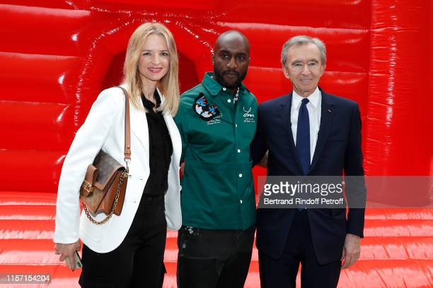 Stylist Virgil Abloh standing between Louis Vuitton's executive vice president Delphine Arnault, Owner of LVMH Luxury Group Bernard Arnault pose...