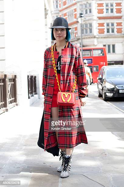 Stylist Virginia Leung wears Jeremy Scott shoes Rihanna for River Island coat Moschino bag SSUR top Diesel hat and Dsquared shirt on day 3 of London...