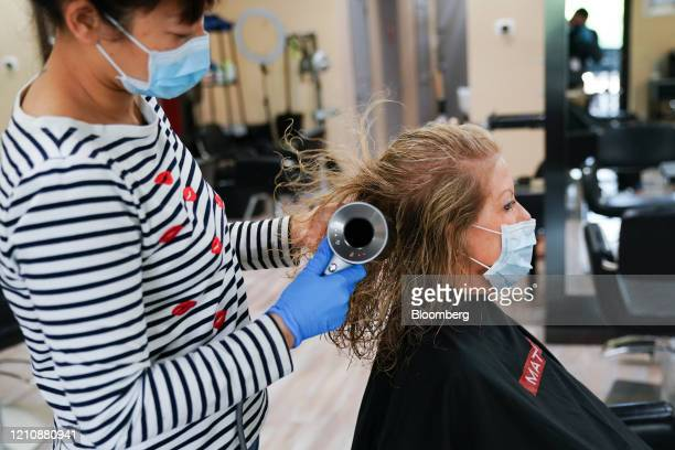 A stylist wearing a protective mask dries a customer's hair at a hair salon in Atlanta Georgia US on Friday April 24 2020 Georgia's hair salons...