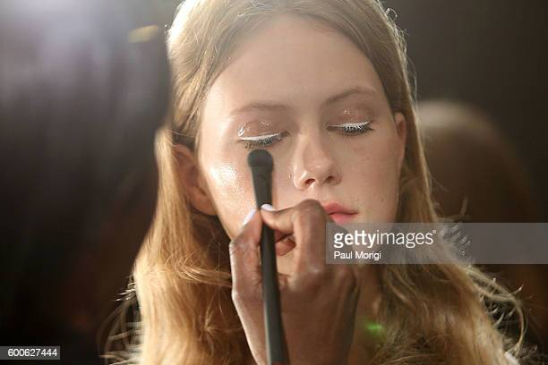 A stylist works on a model's makeup backstage during the Noon By Noor fashion show during New York Fashion Week The Shows September 2016 at The...