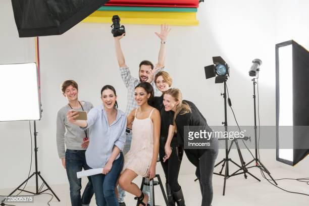 Stylists, model and photographer taking smartphone selfie in photography studio