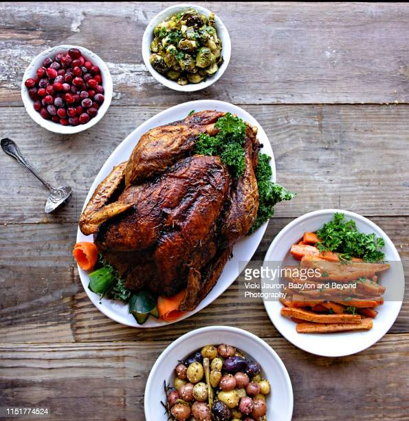 stylized display of turkey dinner with accompaniments on rustic wood table - old fashioned thanksgiving stock photos and pictures