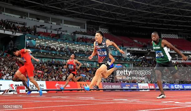 Su Bingtian of China Tosin Ogunode of Qatar and Ryota Yamagata of Japan cross the finish line in the Men's 100m final at the GBK Main Stadium on day...